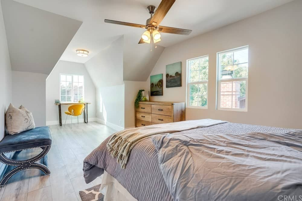 This spacious Cottage-style bedroom has a traditional bed with a green velvet cushioned bench by its foot. Across from it is a lovely nook by the window perfect for the study area within its cove ceiling and matching bright walls.
