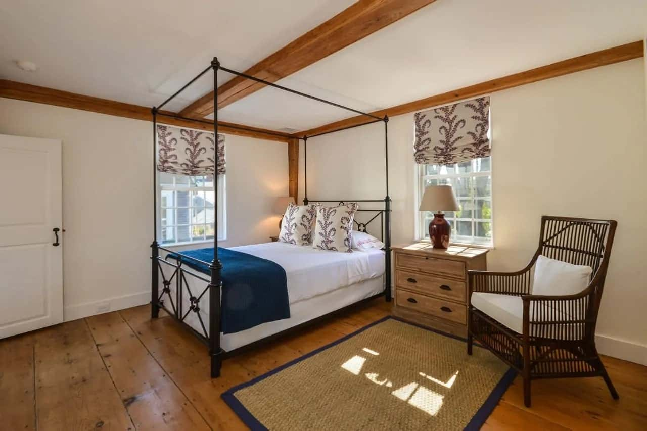 The main feature of this Cottage-style bedroom is the gorgeous and charming wrought iron four-poster bed that contrasts the white cushions and the light tones of the walls and ceiling that has exposed wooden beams matching the floor.
