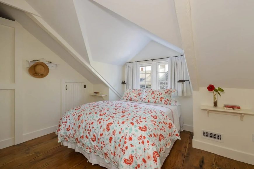 This Cottage-style bedroom has a bed with colorful floral sheets that makes it stand out against the bright white walls and arched ceiling of this Cottage-style bedroom. These are all contrasted by the dark hardwood flooring.