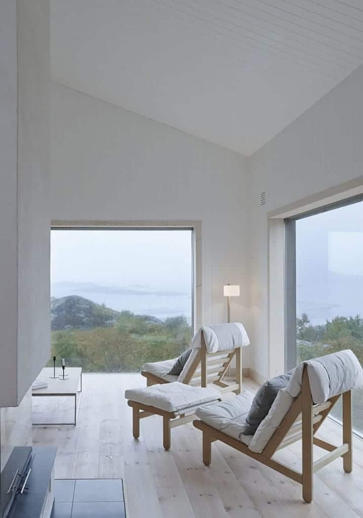 This Cottage-style living room is surrounded by large glass walls that give an amazing view of the surrounding mountainside. This is the focus of the couple of wooden cushioned chairs that pairs well with the light hardwood flooring.