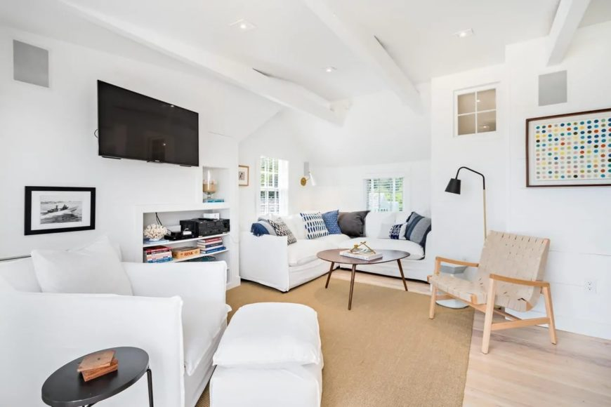 This small living room makes up for its small space with comfort filling the corner area with a lovely white L-shaped sofa matching with the white cushioned armchair across from the brown area rug on the light hardwood flooring.