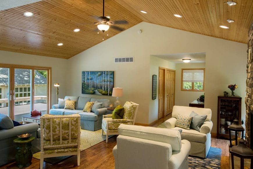 This is a Cottage-style living room with two parts under one tall cathedral ceiling. The part on the left has has a couple of light gray couches matching with the painting on the wall. The part on the right has a couple of cushioned armchairs warmed by the stone fireplace.