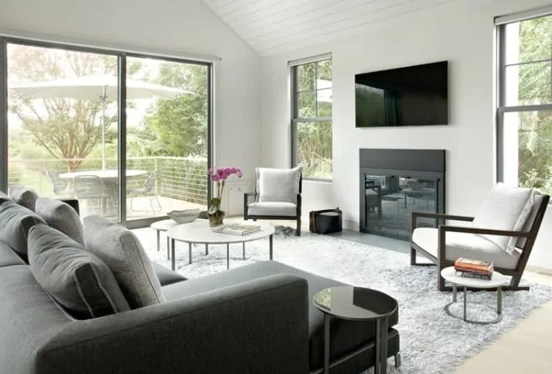 The abundance of natural lights in this Cottage-style living room is a nice touch for the dark gray L-shaped sectional sofa and the modern fireplace it faces. This fireplace is topped with a wall-mounted TV flanked by tall windows.