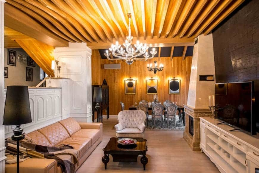 The main feature of this Cottage-style living room is the gorgeous and unique wooden ceiling and its cascading exposed wooden beams that glow from the light of the modern chandelier. This sets a nice background for the brown leather sofa and the light hardwood flooring.