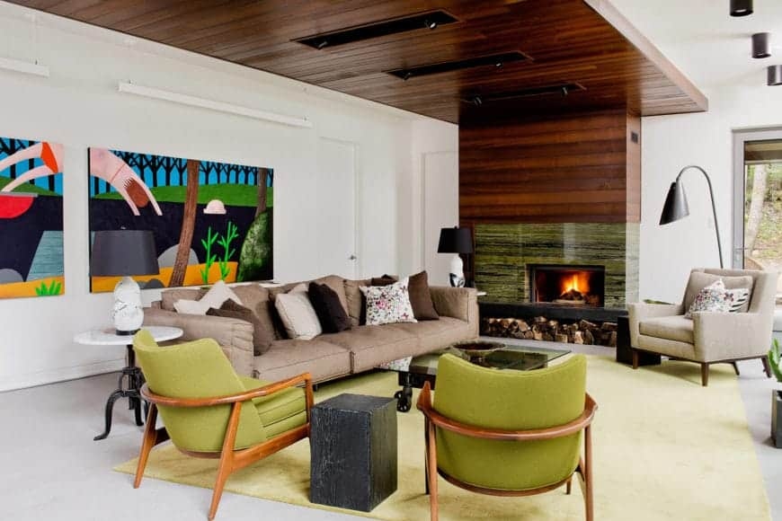 The long brown sofa of this Cottage-style living room is complemented by the couple of large colorful painting mounted on the white wall behind it. This is paired with a couple of green leather armchairs that match the green marble inlay of the fireplace.