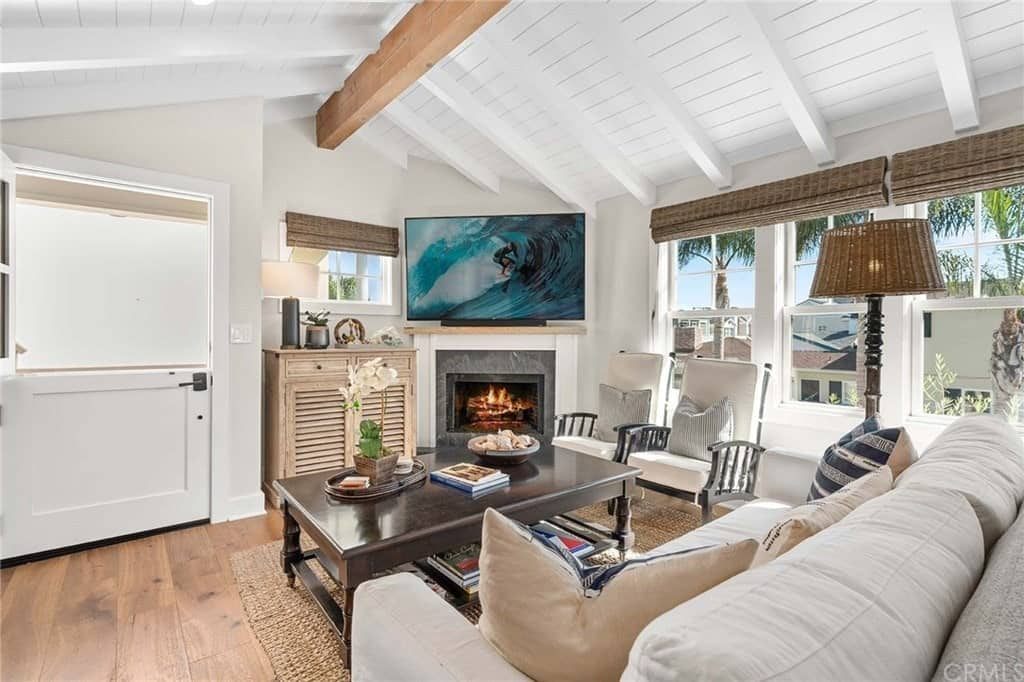 The charming low cathedral ceiling with exposed wooden beams adds a bit of coziness to this Cottage-style living room that makes the white sofa and the two wooden armchairs with cushions seem more comfortable warmed by the fireplace with a TV above.