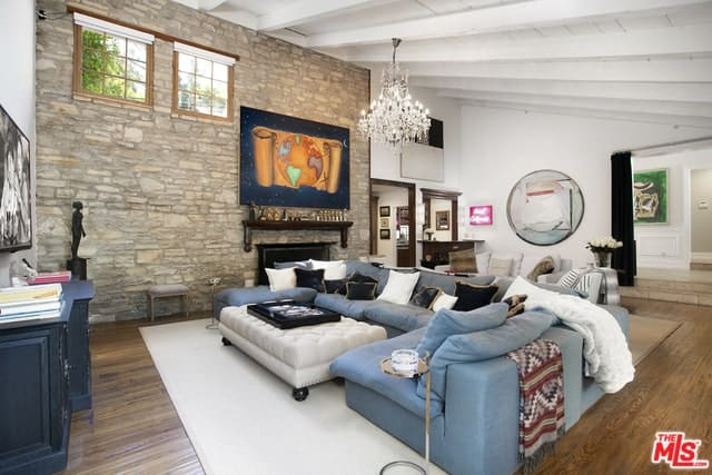 The charming wooden shed ceiling of this Cottage-style living room has exposed white beams and hangs a crystal chandelier over the gray U-shaped sectional sofa paired with a cushioned ottoman for a coffee table. These are all over a large white area rug on top of the hardwood flooring.