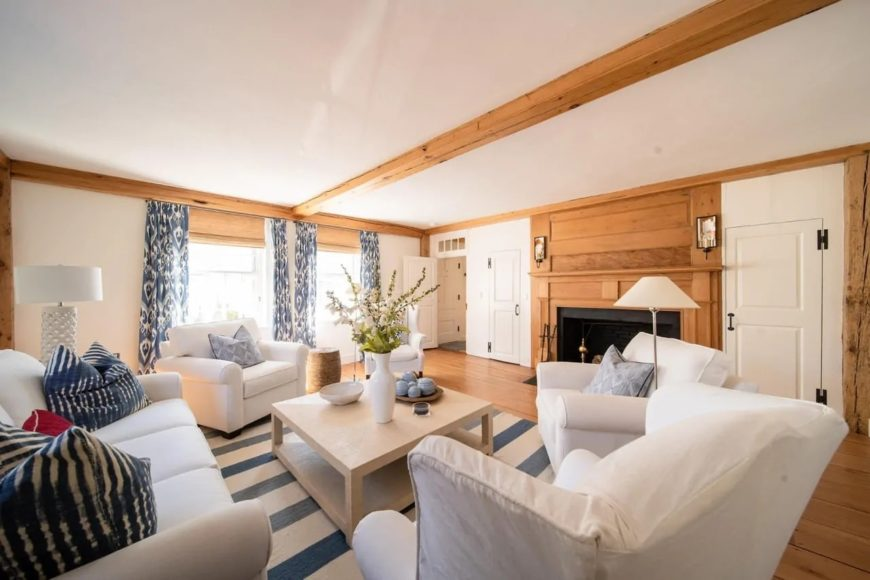 This Cottage-style has a stand-out blue-striped area rug that matches well with the pillows on the sofa and armchairs as well as the blue patterned curtains flanking the windows. These are all complemented by the wooden elements of the flooring, exposed beam of the ceiling as well as the wooden mantle of the fireplace.