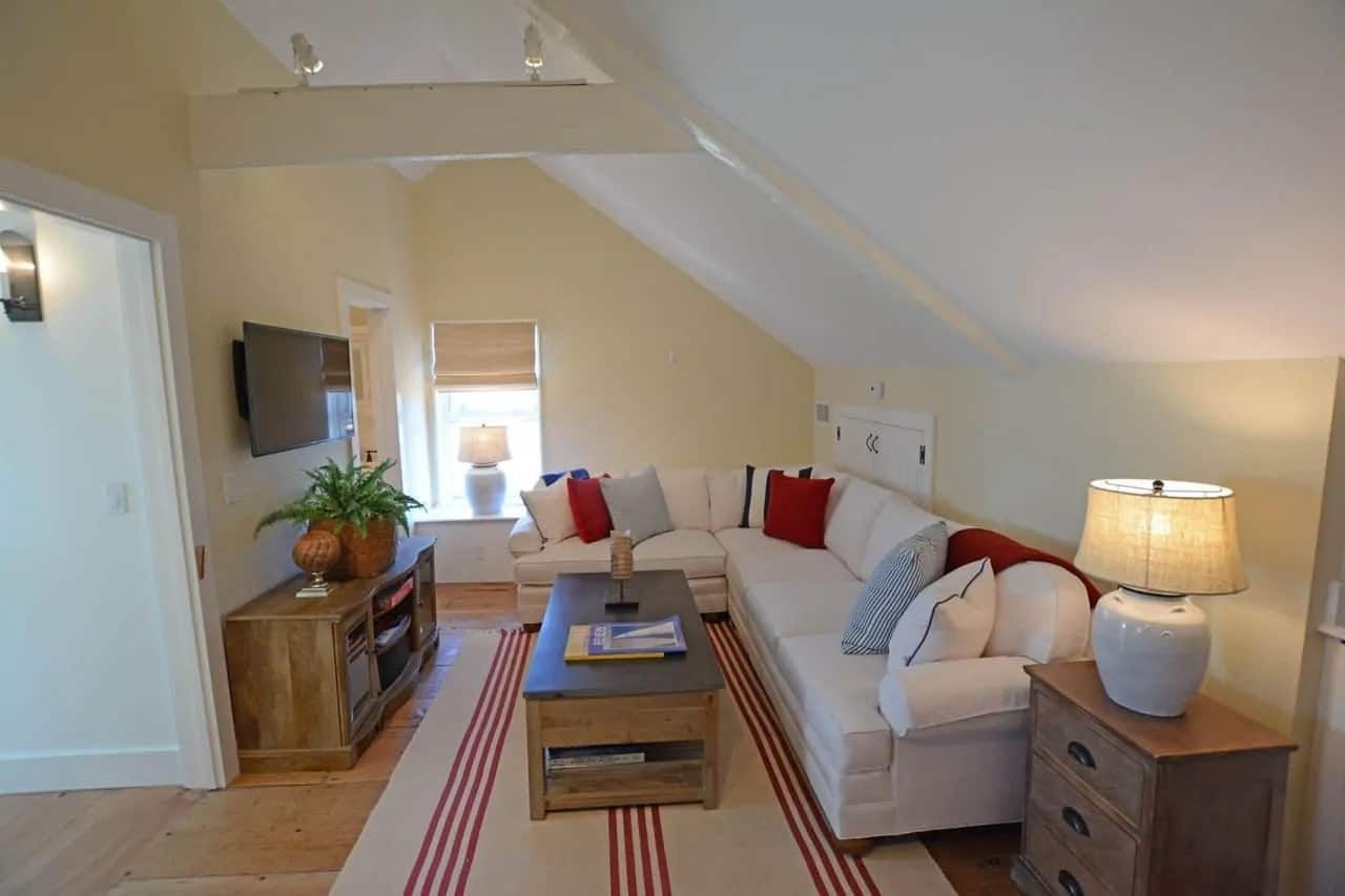 This small Cottage-style living room has a cozy quality to its white low cathedral ceiling with exposed beams. It matches well with the white L-shaped sectional couch facing the wooden coffee table and the wall-mounted TV.