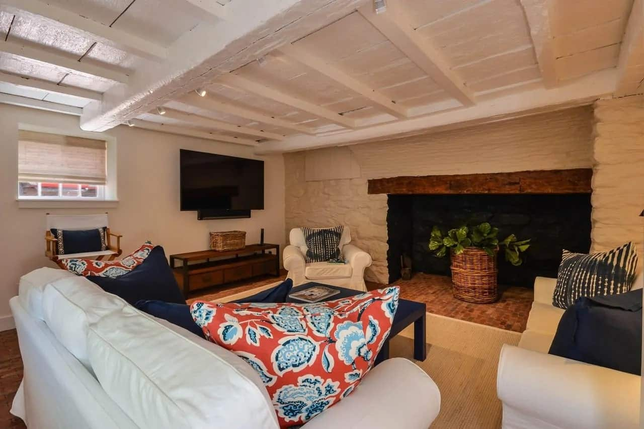 This Cottage-style living room has a rustic textured white ceiling with exposed beams. You can tell there used to be a fireplace at the side but it is instead repurposed to house a potted plant that brings color to the beige walls and white sofa set.