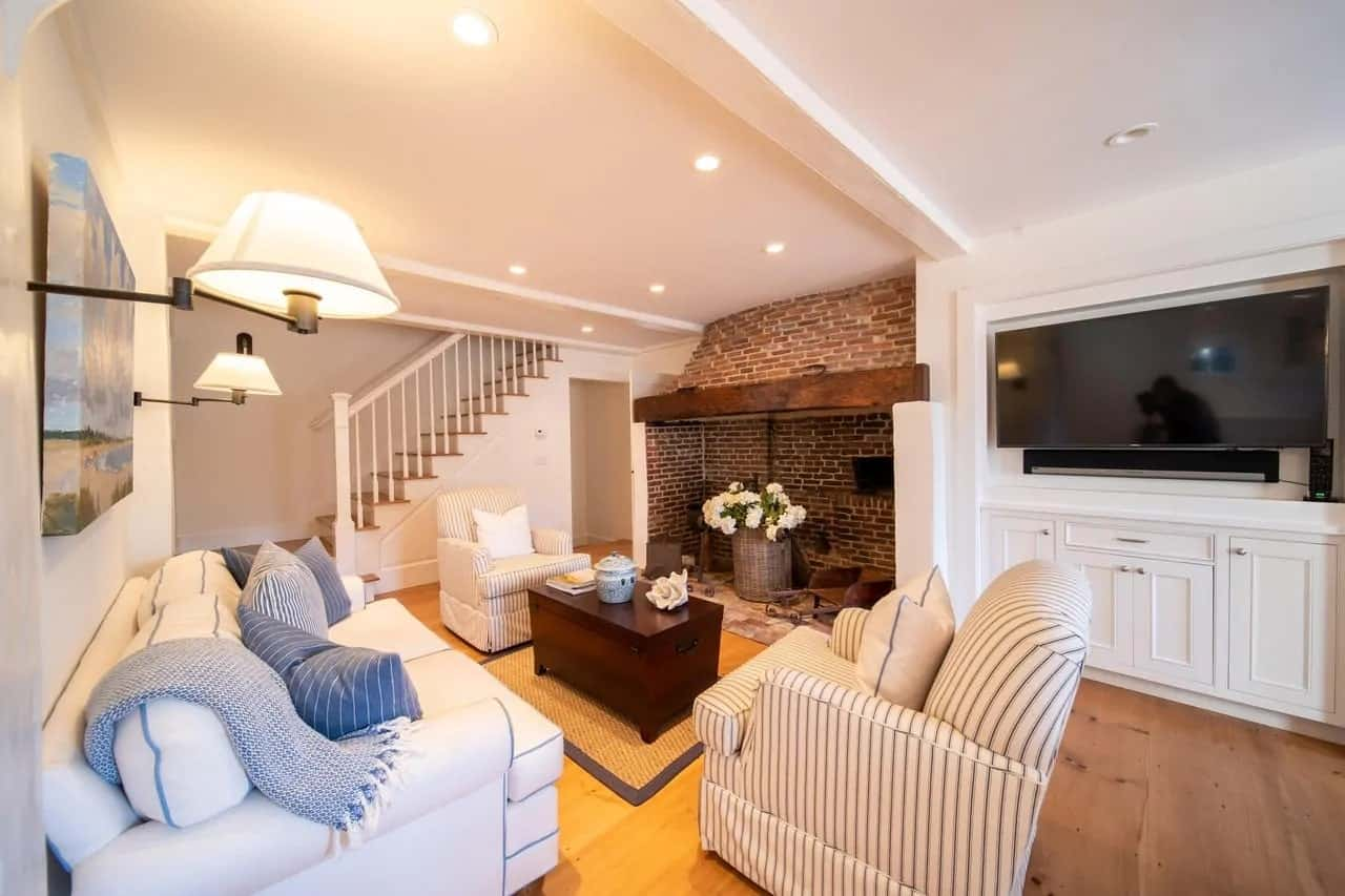 This Cottage-style living room also has a repurposed fireplace retaining its red brick structure for an aesthetic quality that elevates the white ceiling, walls and the light tones of the sofa set.