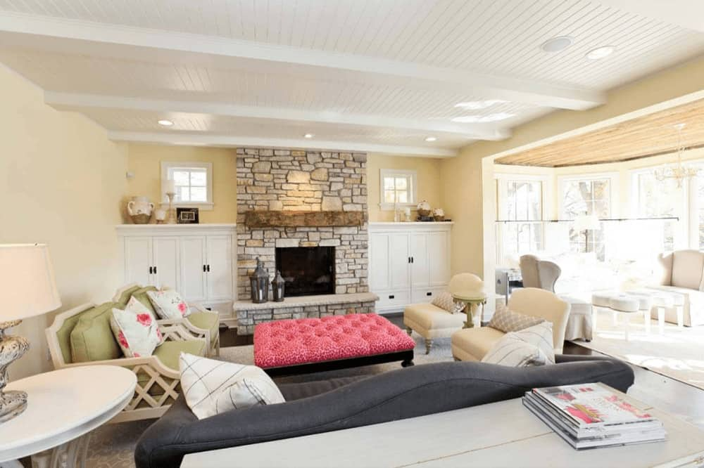 A pink tufted ottoman stands out in this living room with cozy seats and a fireplace lined with rustic wood beam. It is flanked by built-in cabinets and white framed windows complementing the shiplap ceiling.