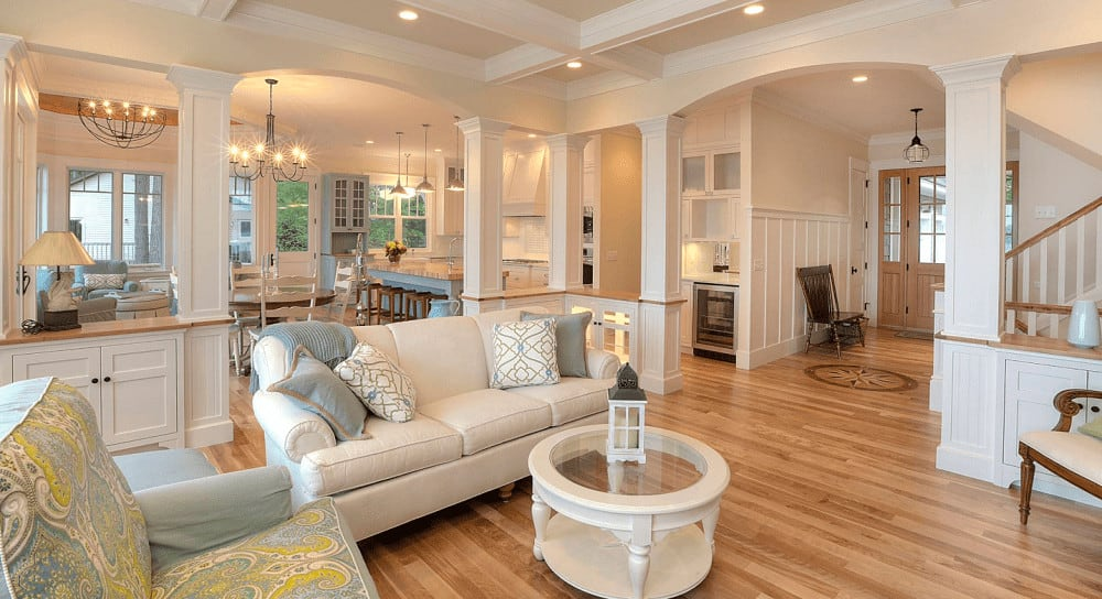 Classic living room with an inviting ambiance featuring hardwood flooring and warm recessed lights mounted on the coffered ceiling. It includes a printed armchair and beige sectional paired with a round glass top coffee table.