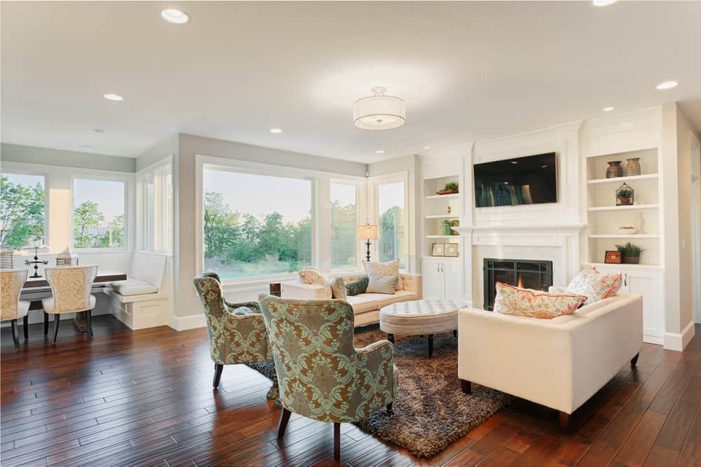 Bright living area showcases white sectional sofas and patterned wingback chairs facing the round tufted ottoman and fireplace with a wall mount TV on top. It is illuminated by a drum semi-flush mount light and recessed ceiling lights.