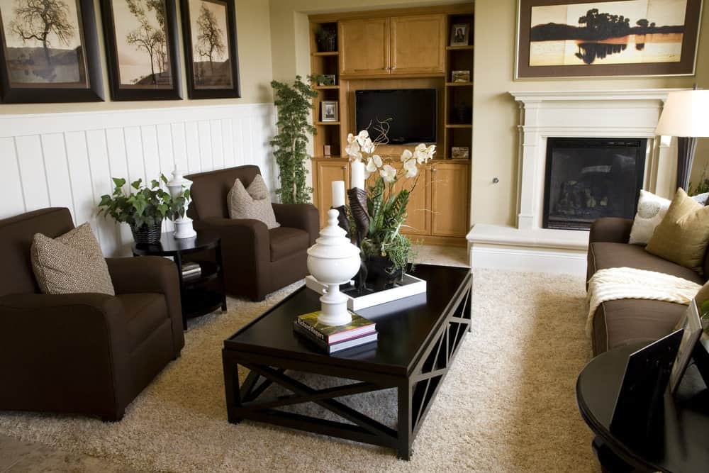 This living room is decorated with landscape painting and black framed artworks mounted above the white beadboard lower wall. It has cozy seats and a fireplace with a built-in cabinet on the side.