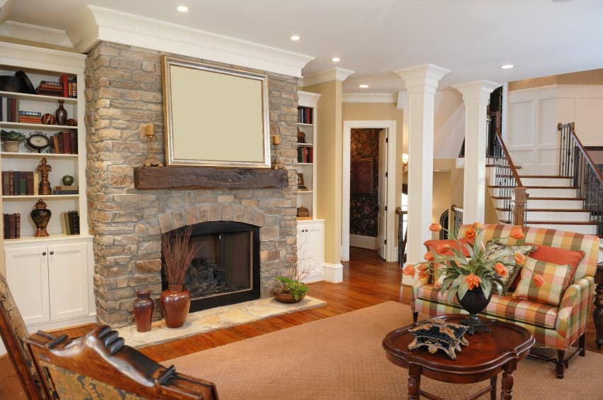 A brick fireplace lined with rustic mantel adds texture in this living room with a plaid sofa and a wooden coffee table topped with a flower vase.