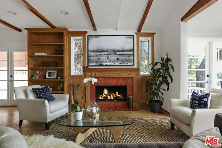 Cottage style living room boasts a fireplace with black and white artwork on top along with a glass top coffee table accompanied by white cushioned chairs accented with deep blue pillows.
