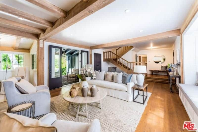Airy living room with comfy seats and a round coffee table over a woven area rug. It has hardwood flooring and a regular white ceiling lined with natural wood beams.