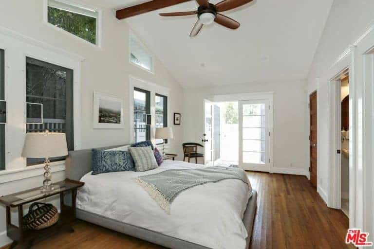 Primary bedroom featuring hardwood flooring and a tall ceiling, along with glass windows. The room offers a large cozy bed and has its own bathroom and closet.