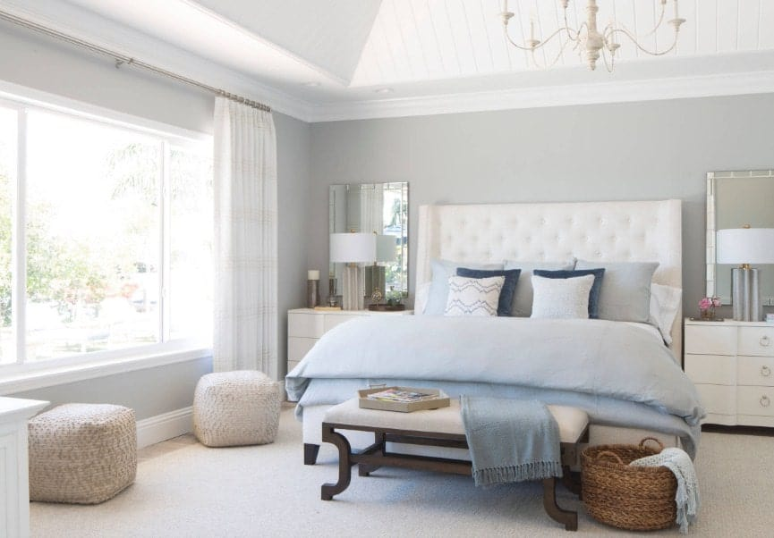 Bright primary bedroom with gray walls and a white ceiling. The room has a large bed and two table lamps, along with a gorgeous chandelier.