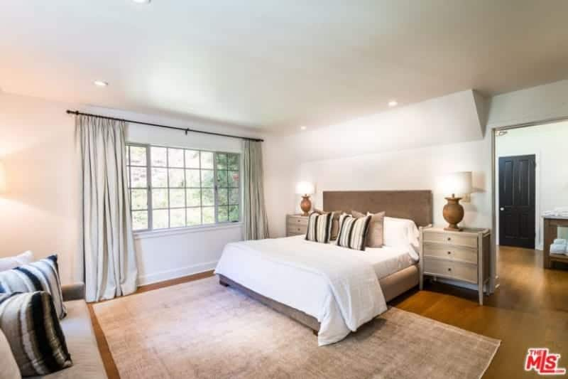 Large primary bedroom featuring hardwood flooring topped by a large area rug. The room has a cozy bed and a comfy couch.