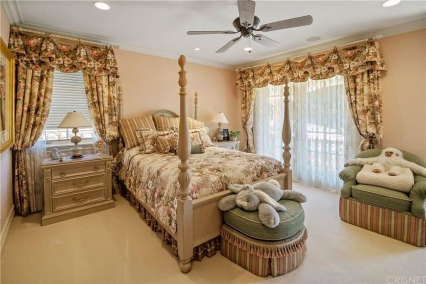 This is a charming Country-style bedroom with a chic demeanor in its floral sheets matching with the floral curtains of the windows covered in sheer cloth to filter the natural lights. This brightens the beige carpeted flooring, four-poster bed and the walls.