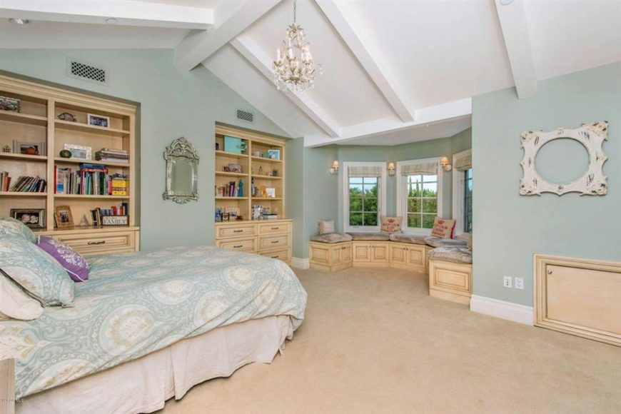 The white cathedral ceiling that has matching white exposed beams hangs a small white chandelier over the traditional bed that has light green patterned sheets to match the light green walls. These walls are adorned with beige cabinetry and a built-in bench at the reading nook by the window.