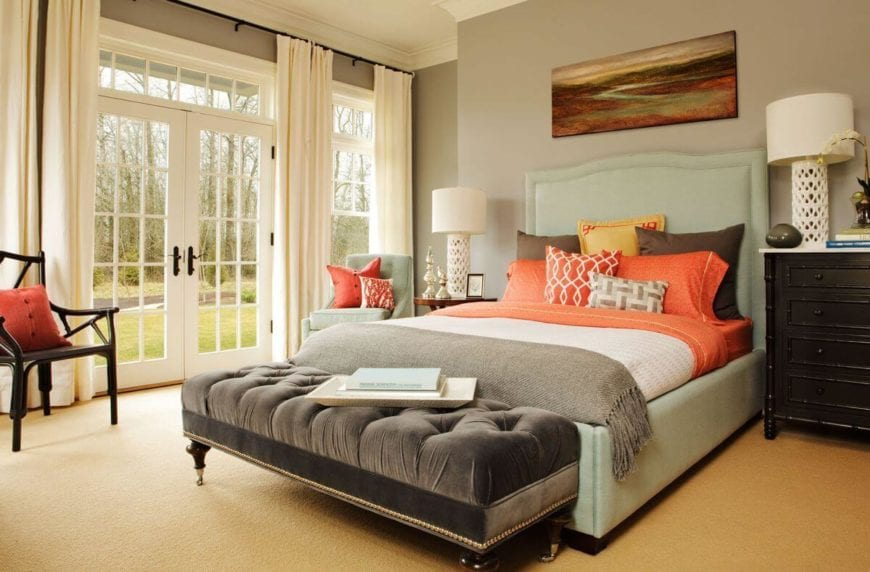 The bright orange tones of this Country-style primary bedroom stands out against the light tones of the light green bed frame and cushioned headboard, light gray walls, beige carpeted flooring and the white ceiling. These lightened further by the natural lights coming in from the glass doors.