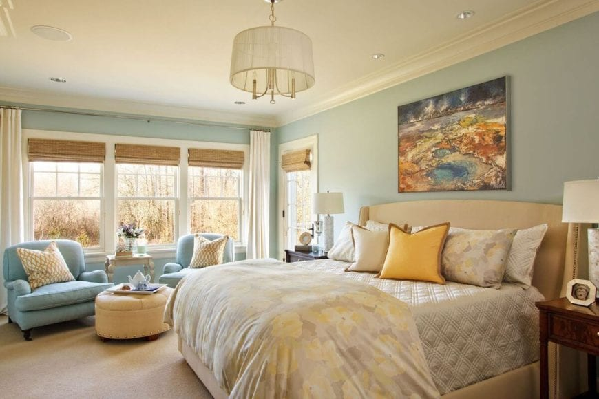 This is a classy Country-style primary bedroom with a champagne bed that has floral sheets and pillows adorned with a colorful abstract painting mounted on the light green wall above the cushioned headboard. This tone of the wall is complemented by the cushioned armchairs on the sitting area by the window.