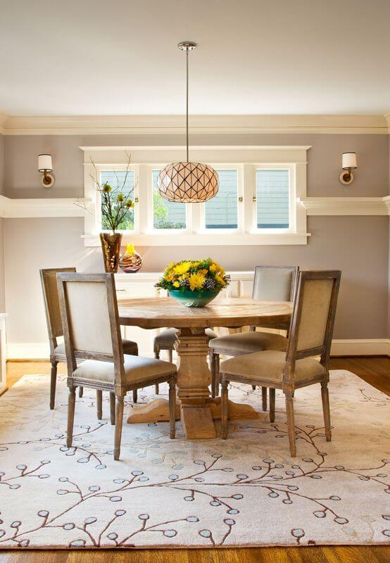 This simple Country-style dining room has a homey quality to its round wooden dining table paired with wooden chairs that has beige cushions matching the charming patterned area rug underneath. This goes well with the light gray walls and bright ceiling.