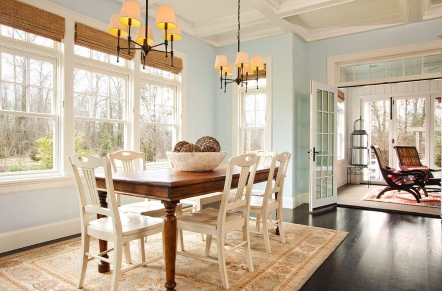 The beige wooden chairs of this Country-style dining room matches well with the beige patterned area rug that covers the dark hardwood flooring. This dark flooring is contrasted by the brilliant light blue walls and white coffered ceiling that hangs a pair of simple chandeliers over the dining set.