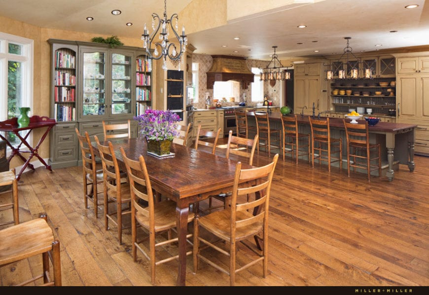 This is a simple informal Country-style dining area beside the kitchen. The beige shed ceiling of this area hangs a simple wrought iron chandelier over the wooden dining table and its wooden chairs that blend well with the hardwood flooring.