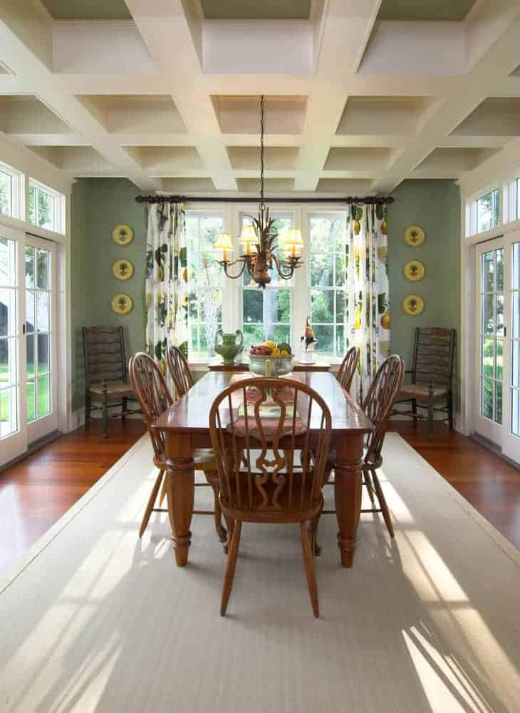 The traditional wooden dining set is separated from the from by a light gray area rug. This hue of the rug is closely related to the coffered ceiling that has a simple chandelier hanging over the table that is complemented by the green walls.
