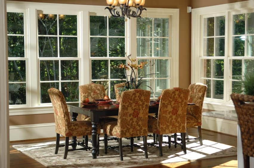 This is a charming and chic formal dining room that is surrounded by a row of windows that feature a lovely landscape scenery outside filled with trees. These windows illuminate the dark wooden dining table and its floral patterned chairs and area rug.