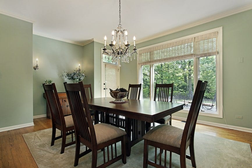 The dark wooden legs of the rectangular dining table matches with the design of the slat backs of the dining chairs. This setup is contrasted by the white ceiling that hangs a wrought iron chandelier matching with the wall mounted lamps of the green walls.