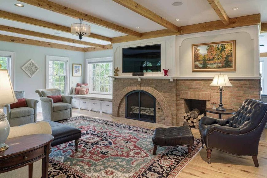 The colorful patterned area rug over the light hardwood flooring and the colorful painting on the white upper wall bring color into this Country-style living room that has a white ceiling dominated by exposed wooden beams. This matches well with the warm brick fireplace with its own firewood storage.