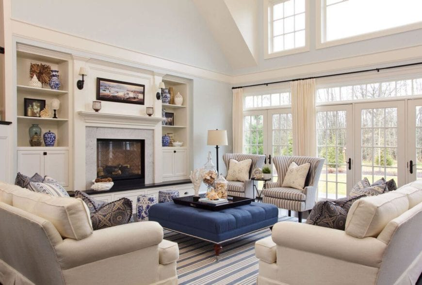 This is a bright and brilliant Country-style living room with amazing light blue walls lightened by the natural lighting provided by the white glass doors and transom windows. This makes the blue cushioned coffee table stand out complemented by the blue striped area rug.