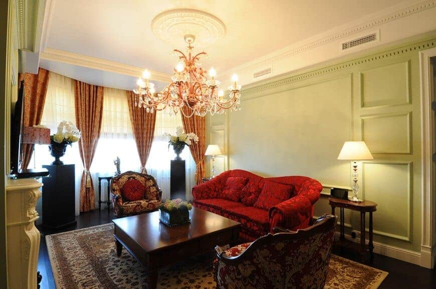 A formal living room boasting an elegant red sofa set and a classy pair of seats along with a center table lighted by a glamorous chandelier. There's a fireplace in the area as well.