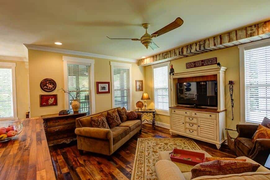 This living room offers an elegant sofa set along with a rustic side table and a large widescreen TV in front, surrounded by yellow walls and has hardwood flooring as well.