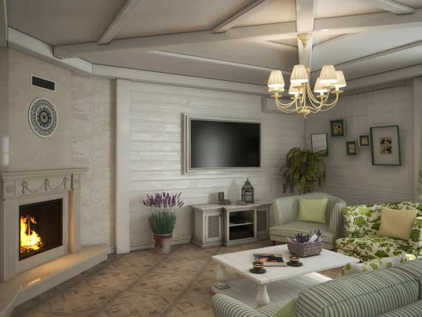 Large Country-style living room boasting elegant seats, a classy fireplace and a large widescreen TV on the wall. The room is lighted by a gorgeous chandelier.