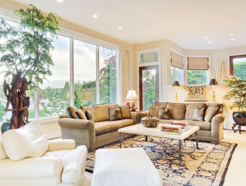 This Country style living room offers an elegant sofa set and a center table situated on top of a classy rug. The room offers large glass windows overlooking the breathtaking surroundings. The home also has indoor plants in the area.