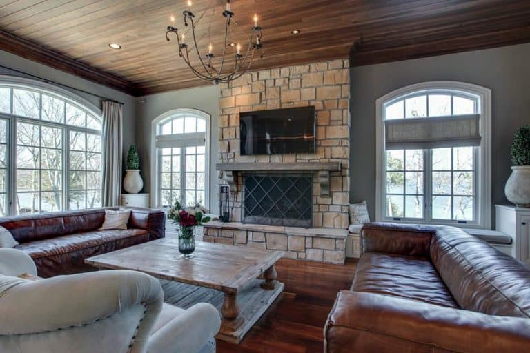 A focused shot at this Country-style living room boasting a couple of leather couches and a large classy fireplace with a large widescreen TV above it.