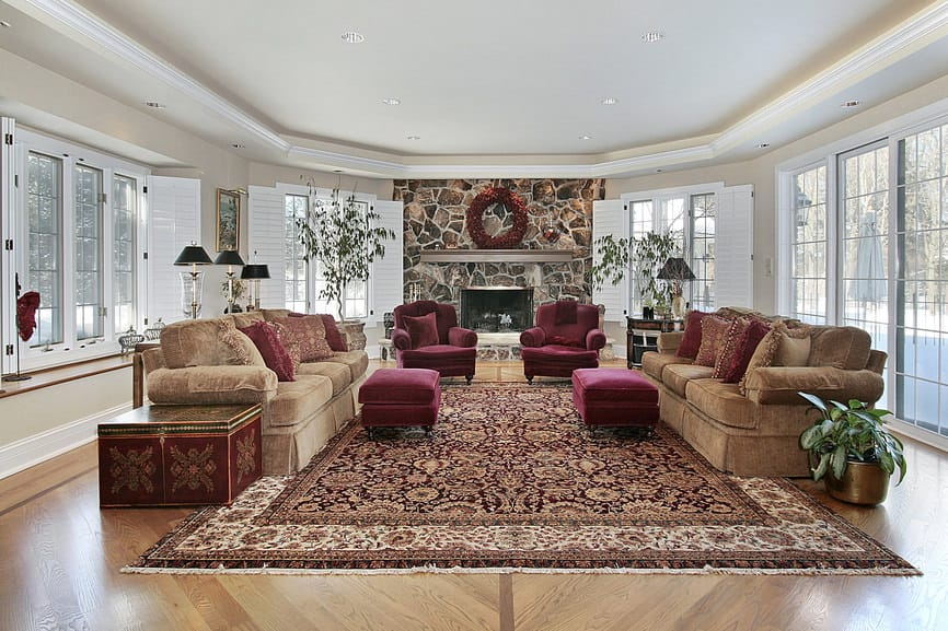 Large formal living room boasting a pair of elegant couches along with red velvet seats with footrests, set on top of a large area rug covering the hardwood flooring. There's a large stone fireplace and a tray ceiling.
