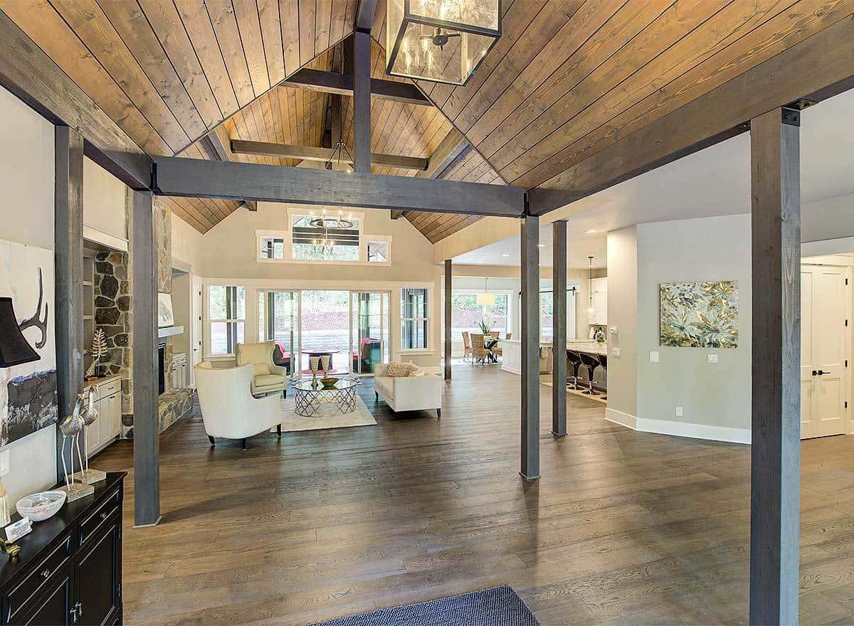This charming foyer has a shiplap wooden cathedral ceiling supported by thin wooden pillars. The ceiling matches with the hardwood flooring complemented by a dark wooden console table on the side.