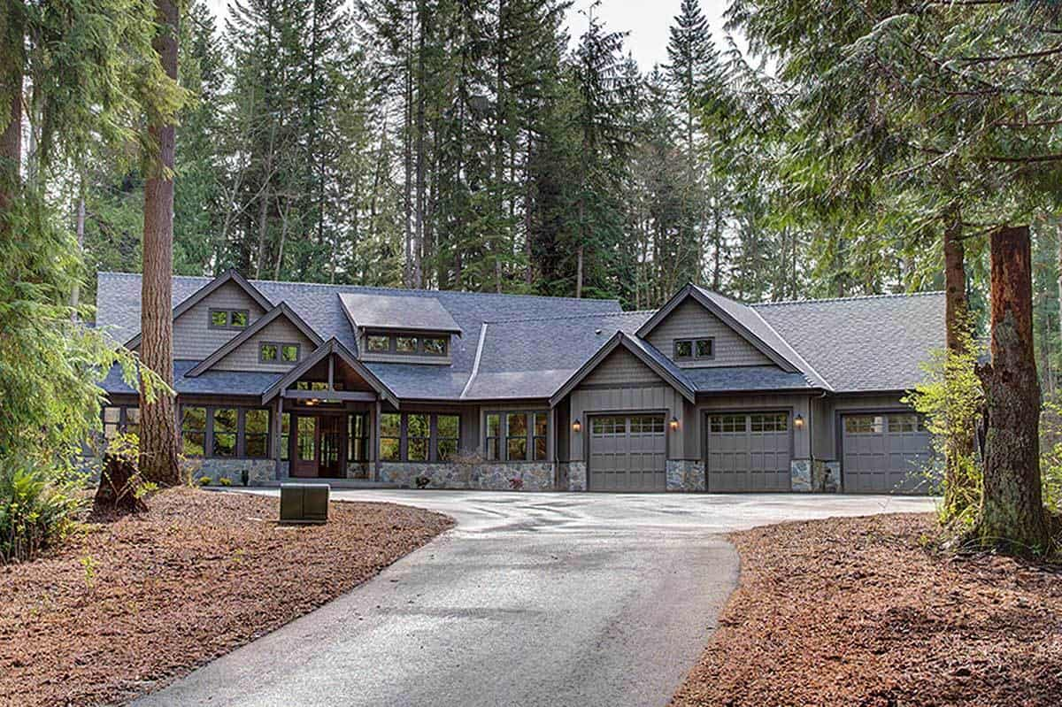 The charming gray tones of the house exterior are complemented by the lush, green and tall pine trees in the background that extend to surround the house and flank the wide concrete driveway that leads to the three gray garage doors and the main entry.