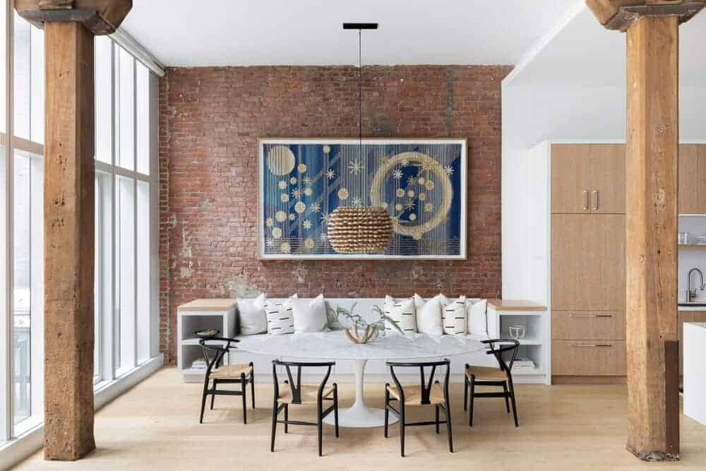 A spacious industrial-style dining room with a large oval-shaped dining table set lighted by a fancy pendant light. The brick wall features a stylish wall decor as well.