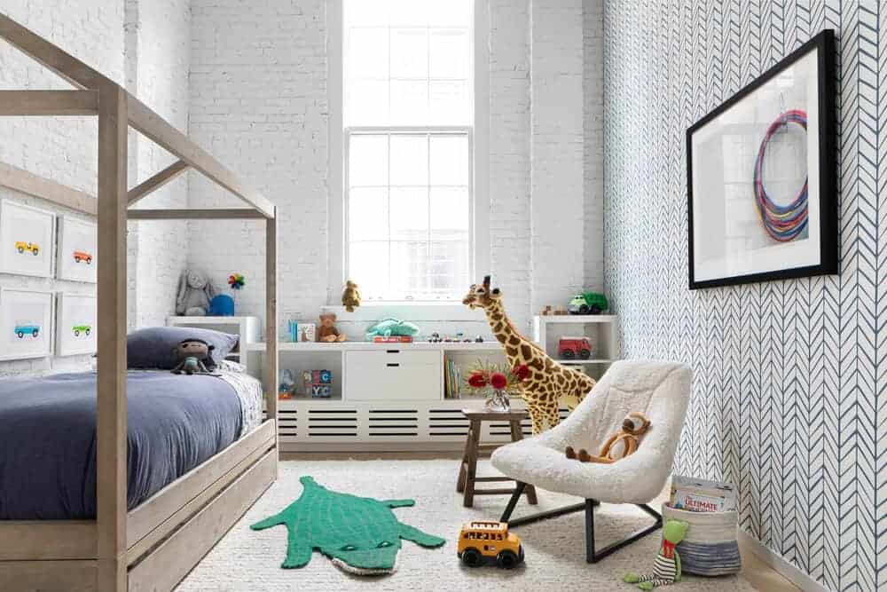 A kids' bedroom featuring a comfy bed with a rustic frame surrounded by stylish walls and a high ceiling. The room also offers a large area rug covering the hardwood flooring.