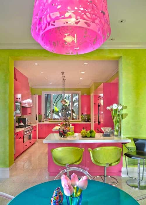 Lime green walls add a striking contrast to the pink cabinetry fitted with wrought iron knobs. This kitchen has tiled flooring and glass-paneled windows inviting natural light in.
