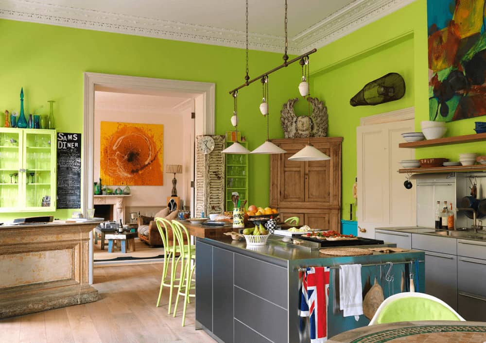 White dome pendants illuminate the gray island bar that's attached with a wooden eating counter. This kitchen has wide plank flooring and vibrant green walls mounted with interesting decor and artwork.