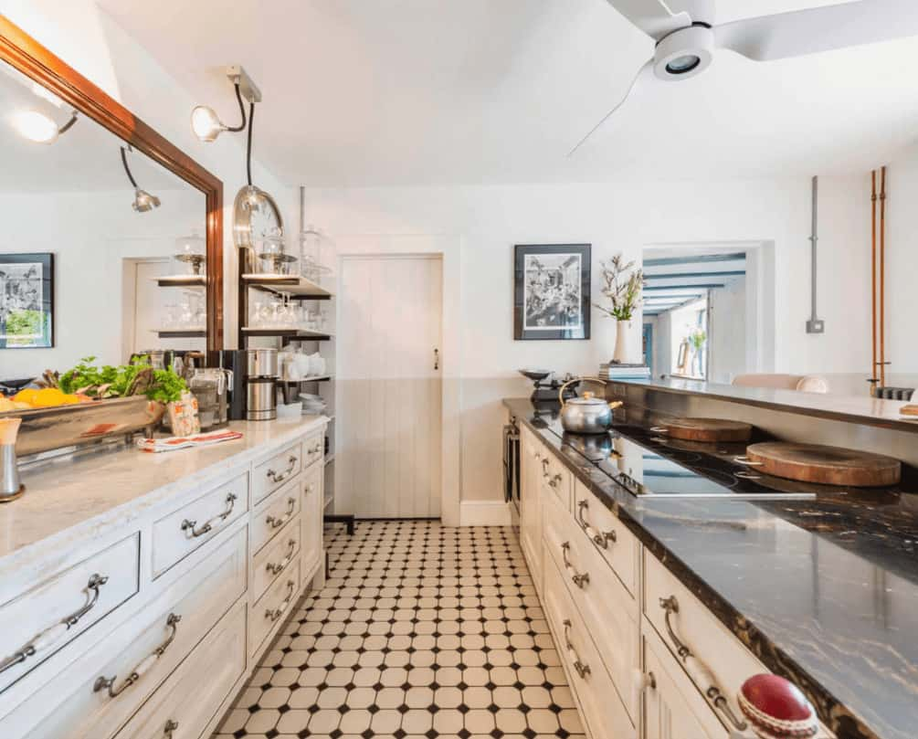 The galley kitchen features white cabinetry with chrome pulls topped with black and white marble counters. It includes a shelving unit and a wooden framed mirror that creates a larger visual space in the room.